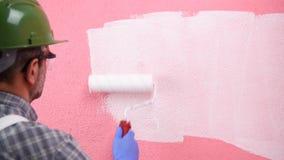 Schilderarbeider die de roze muur met witte verf schilderen De bouw stock footage