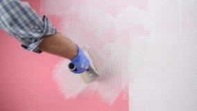 Schilderarbeider die de roze muur met witte verf schilderen De bouw stock videobeelden