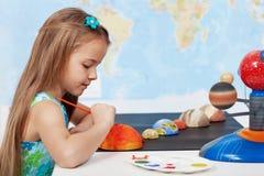 Schilderend de zon - schoolmeisje in wetenschapsklasse stock foto