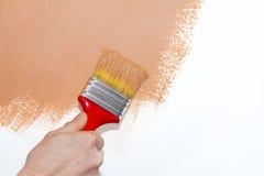 Schilderend een bruine muur stock fotografie