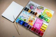 Schilderende borstel en geschilderd palet Stock Afbeeldingen
