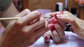 Schilderende spijkers De manicure smeert de spijker met lijm en past bergkristallen met een speciaal hulpmiddel toe stock footage