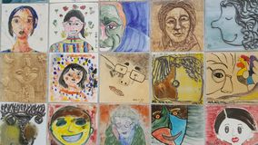 Schilderijen en gebeeldhouwde gezichten van mensen op de muur voor gedenkschrift stock afbeelding