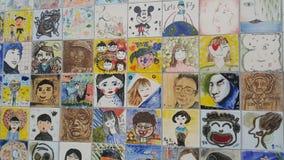 Schilderijen en gebeeldhouwde gezichten van mensen op de muur voor gedenkschrift stock afbeeldingen