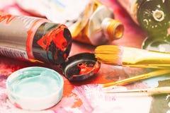Schilderswerkplaats met buizen van veelkleurige olieverf en penselen op geschilderd document dicht omhoog met selectieve nadruk Stock Foto