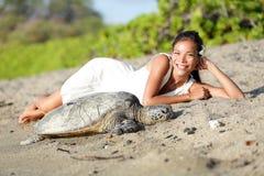 Schildpad en vrouw die op strand, Groot Eiland Hawaï liggen Stock Foto