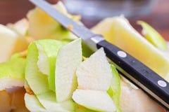 Schillen groene appel, stukken van schil en een mes die op bovenkant liggen royalty-vrije stock foto