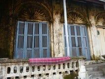 Schimmelndes britisches Kolonialportal mit blauen Fensterläden, wie herein gesehen Stockbilder