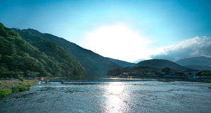 Schimmernder flacher Fluss mit Rollenbergen bei Arashiyama, Japan Stockbild