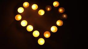 Schimmerndes Licht von den Kerzen Kerzen funkelnder Hintergrund Helle Kerzen des Tees die Form eines Herzens bildend Liebesthemak stock footage