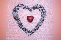 Schimmerndes rotes Herz innerhalb des symbolischen Herzens von Kaffeebohnen auf sy Stockfotografie