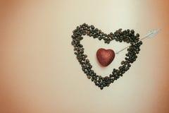 Schimmerndes rotes Herz innerhalb des symbolischen Herzens von Kaffeebohnen pier Lizenzfreies Stockbild