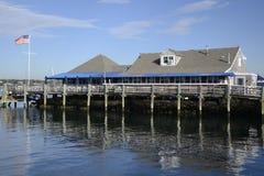 Schindelgebäude durch Wasser und Dock Lizenzfreie Stockfotos