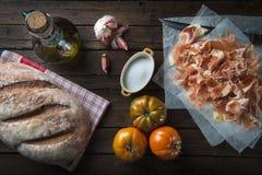 Schinken mit Brot, Tomate, Knoblauch und Olivenöl stockbilder