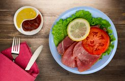 Schinken mit Salat, Tomate und Zitrone auf einer Platte Stockbilder