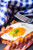 Schinken und Ei Speck und Ei Gesalzenes Ei und besprüht mit schwarzem Pfeffer und grüner Krautdekoration Lizenzfreies Stockfoto