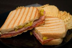 Schinken und Pastrami panini mit Kräuselungschips stockfotografie