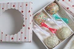 Schiocchi del dolce decorati con un arco della treccia, imballato in un contenitore di regalo immagine stock