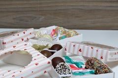 Schiocchi del dolce decorati con un arco della treccia, imballato in un contenitore di regalo fotografie stock