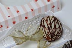 Schiocchi del dolce decorati con un arco della treccia, imballato in un contenitore di regalo immagini stock libere da diritti