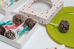 Schiocchi del dolce decorati con un arco della treccia, imballato in un contenitore di regalo Altri dolci sono vicini vicino sul  immagini stock libere da diritti