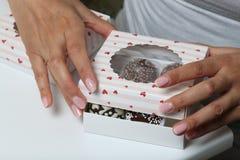 Schiocchi del dolce decorati con un arco della treccia, imballato in un contenitore di regalo La donna chiude la scatola immagini stock libere da diritti