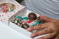 Schiocchi del dolce decorati con un arco della treccia, imballato in un contenitore di regalo La donna chiude la scatola fotografia stock libera da diritti