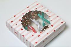 Schiocchi del dolce decorati con un arco della treccia, imballato in un contenitore di regalo Nel coperchio della scatola ? una f fotografia stock