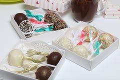 Schiocchi del dolce decorati con un arco della treccia, imballato in un contenitore di regalo Vicino sono le tazze di cioccolato  fotografie stock