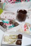 Schiocchi del dolce decorati con un arco della treccia, imballato in un contenitore di regalo Vicino sono le tazze con cioccolato immagini stock