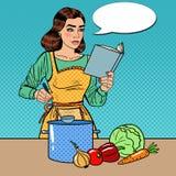 Schiocco Art Beautiful Housewife Cooking Soup nella cucina con il libro delle ricette Immagine Stock