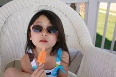 Schiocco asiatico del ghiaccio di cibo della ragazza con i vetri di sole Fotografie Stock