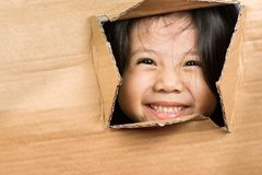 Schiocco asiatico impertinente e così sveglio della bambina dalla scatola di cartone Immagini Stock