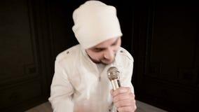 Schiocco della roccia del vocalist dell'uomo di punta con una barba alla moda in vestiti bianchi ed in un cappello con un microfo stock footage