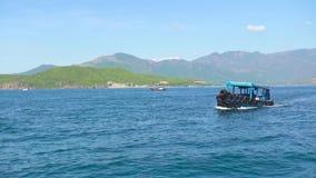 Schip die in blauwe overzees op groen berglandschap drijven Boot die in turkoois zeewater, groene berg en duidelijke hemel varen stock videobeelden