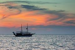 Schip die tegen kleurrijke hemel na zonsondergang over het overzees varen Stock Foto