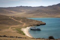Schip in een kleine baai Steenachtige, verlaten kust De zonnige dag van de zomer De weg gaat in de afstand stock afbeelding