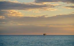 Schip en Bewolkte Hemel bij Zonsondergang over het Overzees Stock Foto