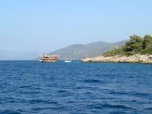 Schip met toeristen dichtbij het rotsachtige groene eiland in het overzees royalty-vrije stock afbeelding
