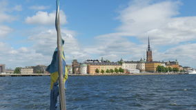 schip met Zweedse vlag die van oude stad, Stockholm, Zweden weggaan stock footage
