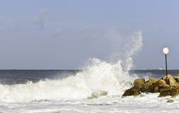 Schip op een achtergrond van de golven die over een golfbreker breken Royalty-vrije Stock Foto