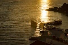 Schip op zee in gouden zonneschijn bij zonsondergang stock afbeelding