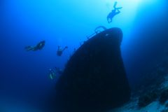 Schipbreuk en duikers Stock Foto