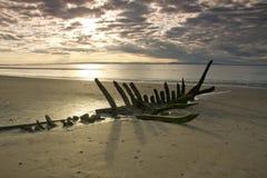 Schipbreuk op een strand bij zonsondergang stock afbeeldingen