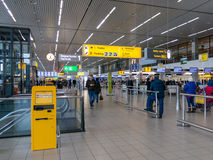 Schiphol Amsterdam Airport departure terminal, Holland. Signs, clock and travellers in departure terminal of Schiphol Amsterdam Airport, Netherlands Royalty Free Stock Photography