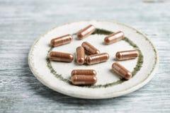 Schisandra chinensis Kräuterkapseln mit gesunder medizinischer Anlage Gesunde Ergänzung auf rustikalem hölzernem Hintergrund lizenzfreies stockbild