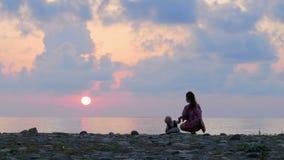Schislivaya-Familie: Mutter, Babysohn auf dem felsigen Seestrand während des Sonnenuntergangs Erziehen Sie Spiel und küssen Sie B stock video