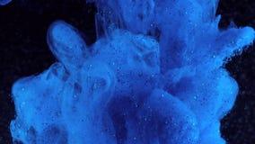 Schitter inkt in water Blauwe verf met fonkelingen bij het zwarte reageren in water die tot abstracte wolkenvormingen leiden kan  stock footage