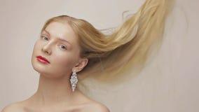 Schitterend blond meisje met langzaam dalend haar Kijk in camera stock videobeelden