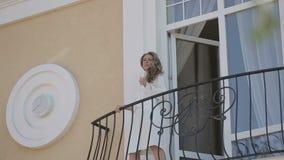 Schitterend blonde in badjas op balkon stock video